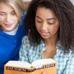 Zwei Schülerinnen lesen im Duden