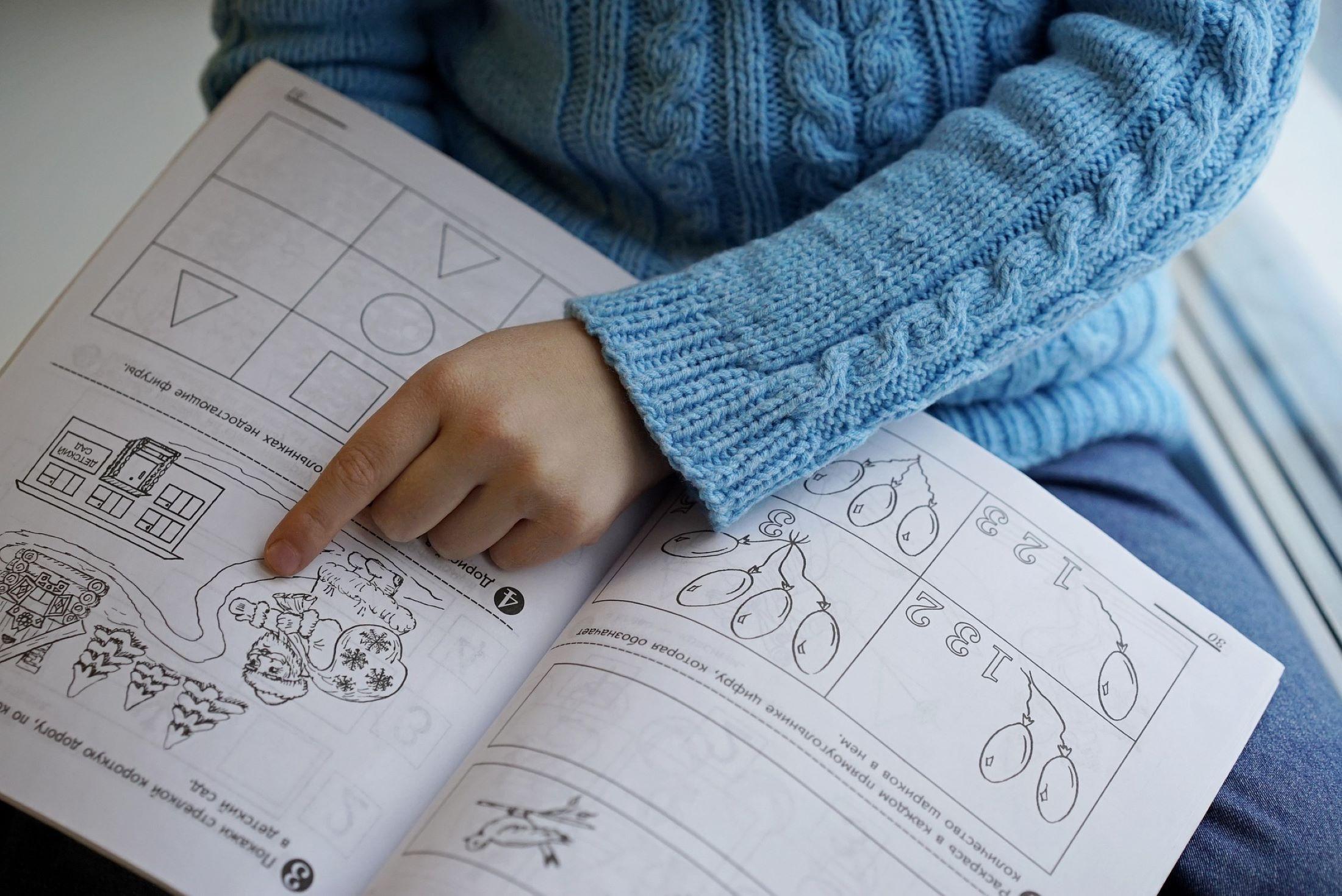 Kind mit Lernheft auf dem Schoß