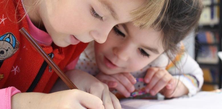 Mädchen tief über ein Heft gebeugt und schreibend