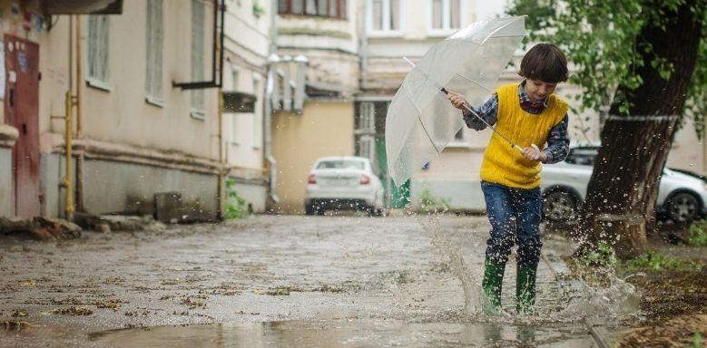 Wasserkreislauf der Erde - Ein Junge mit Regenschirm der durch Pfützen springt
