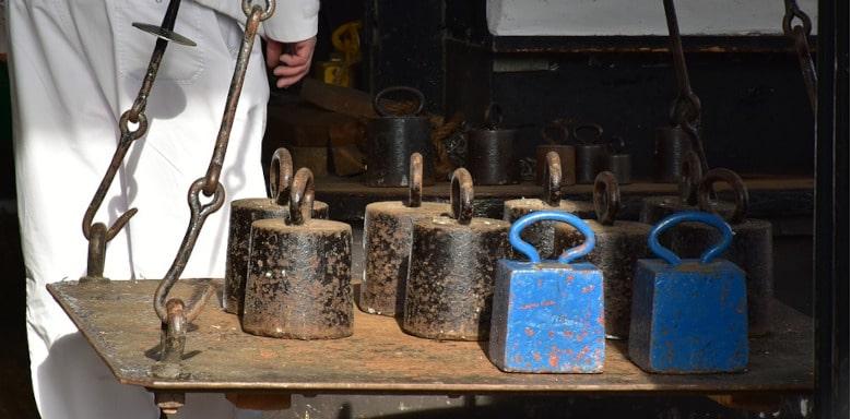 Verschiedene Gewichte auf einer alten Waage - Gewichtseinheiten