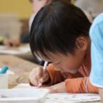 Kleiner Junge beim Lösen von Aufgaben - Gewicht umrechnen