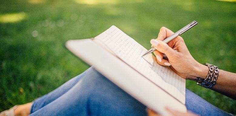 Frau schreibt in ein Buch - Rezension schreiben