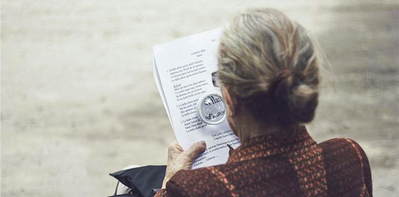 Frau liest Text mit Lupe - neue Rechtschreibung ß