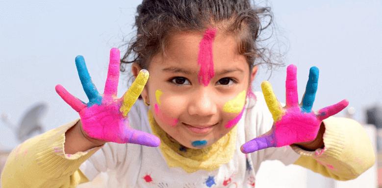 Kind mit farbverschmierten Händen