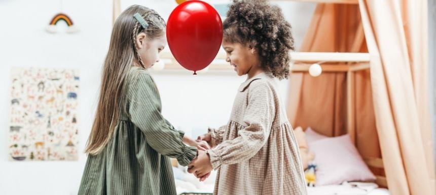 zwischen der Stirn zweier Mädchen ist ein Ballon, sie halten sich an den Händen