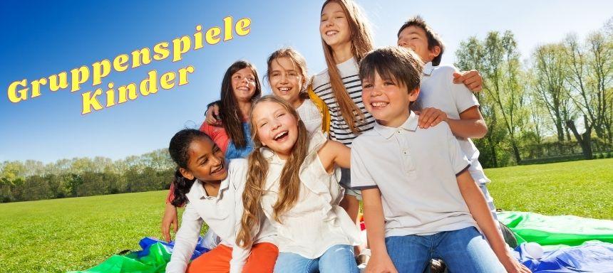 Gruppe an Kindern draußen auf Schals lachen, oben links steht Gruppenspiele Kinder