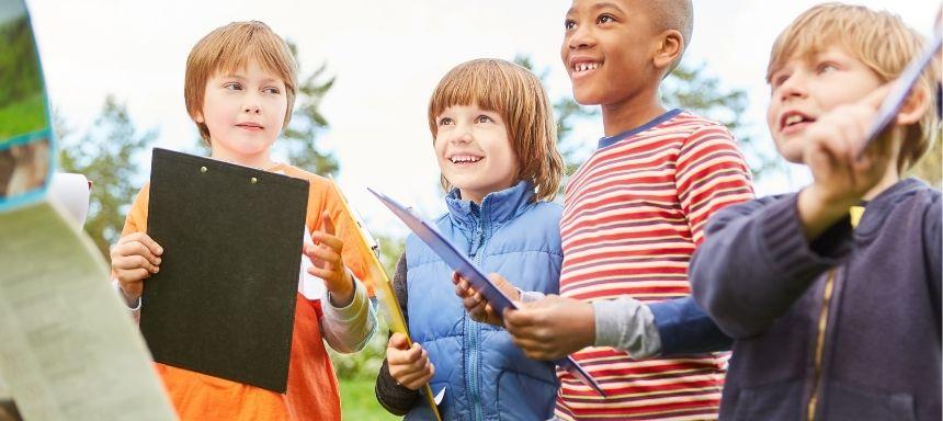 vier Kinder mit Klemmbrettern bekommen Anweisungen
