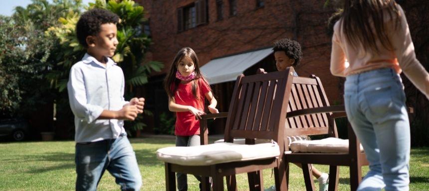 vier kinder tanzen um drei Stühle