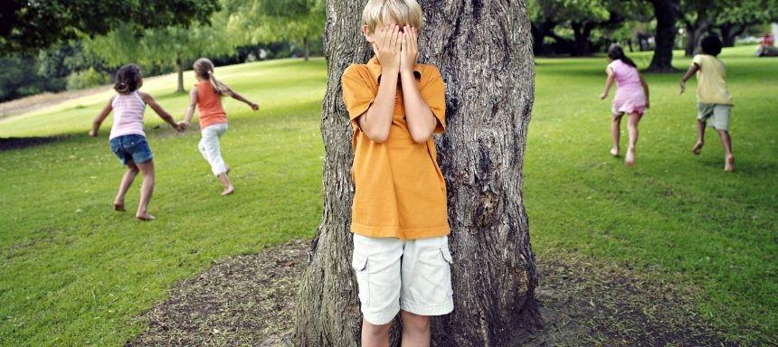 Kind in der Mitte steht hinter Baumstamm und hält sich die Augen, je 2 Kinder pro Seite rennen weg