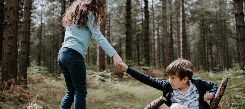Mädchen hilft Jungen aufzustehen