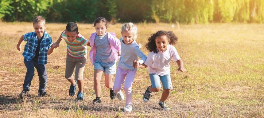 5 Kinder nebeneinander bilden eine Kette und rennen