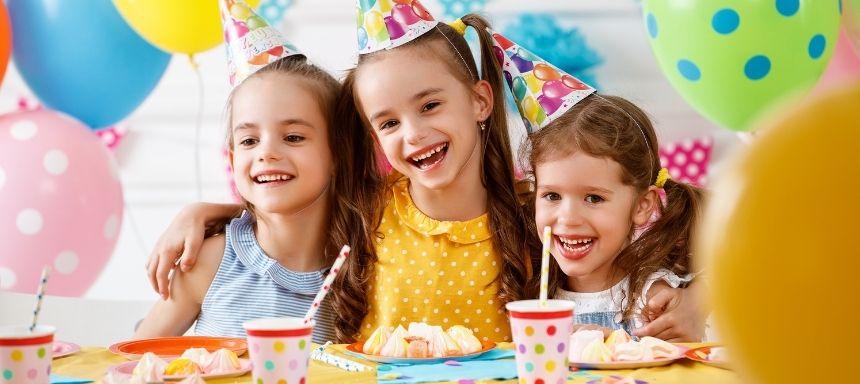 drei Mädchen auf einem Kindergeburtstag essen Kuchen und halten sich im Arm