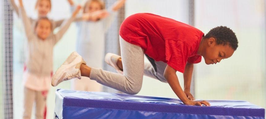 Kind springt seitlich über einen blauen Matratzenturm, im Hintergrund jubeln Kinder