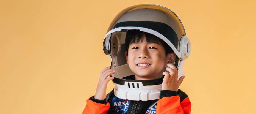 Kind setzt Astronautenhelm auf vor gelbem Hintergrund in NASA Anzug