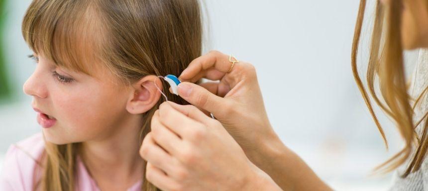 Arzt setzt Mädchen Hörgerät ins Ohr