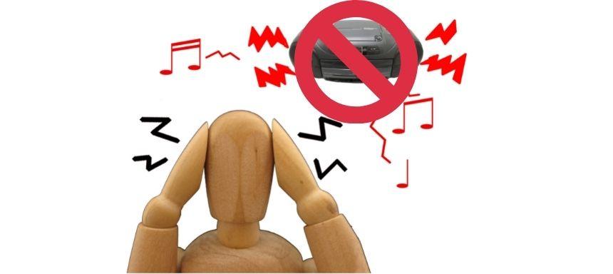 Holzpuppe hält sich Hände an den Kopf, Radio ist durchgestrichen mit vielen Musiknoten