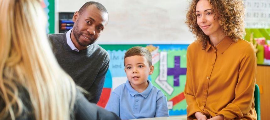 eltern mit kind in der Mitte reden mit Lehrerin