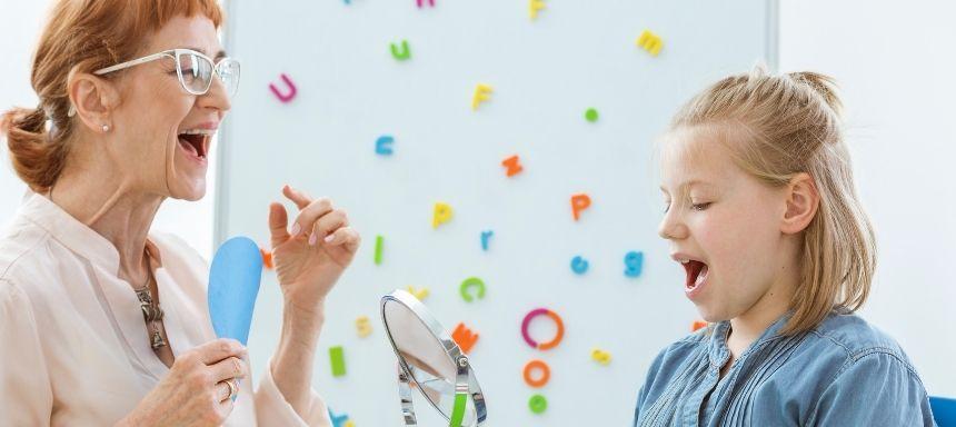 Logopädin und Kind übt vor Spiegel Übungen