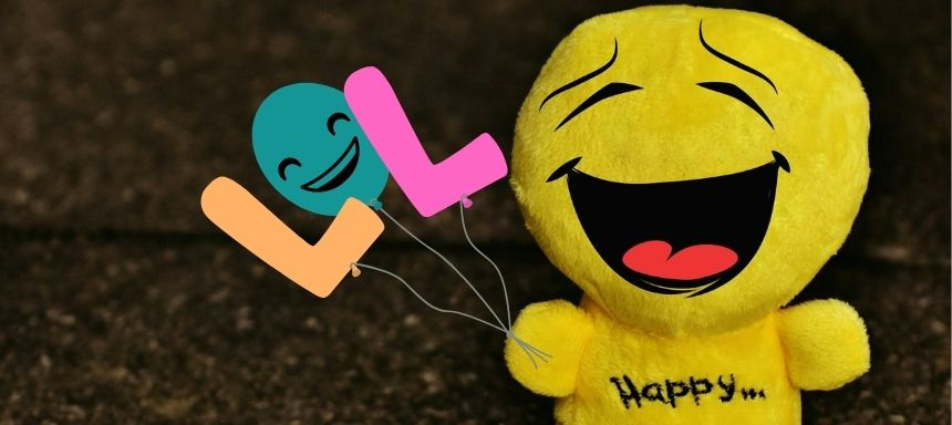 ein lachendes gesicht als Plüschtier hält LOL Luftballons
