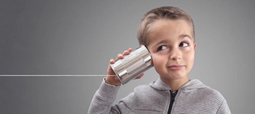 Junge hält Blechdose mit Kabel ans Ohr