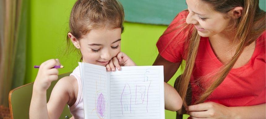 Frau sieht Mädchen an, dass eine Zeichnung von sich in einem Heft zeigt