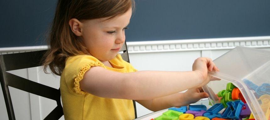 Mädchen spielt mit Eimer voller Holzbuchstaben