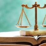 Wirtschaftsrecht - Wirtschaftsrecht - Waage auf Buch stehend